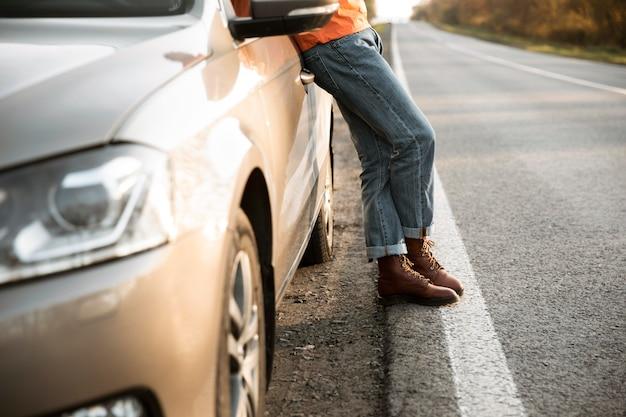 Vista laterale dell'uomo appoggiato all'auto durante un viaggio su strada