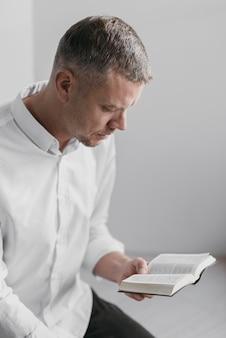 Uomo di vista laterale che legge un libro sacro
