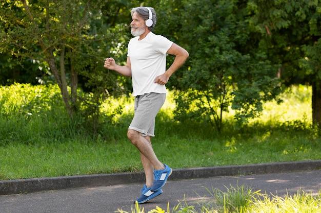 Uomo di vista laterale che corre all'aperto