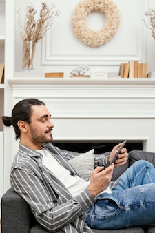 Uomo di vista laterale che si siede sul divano con un tablet