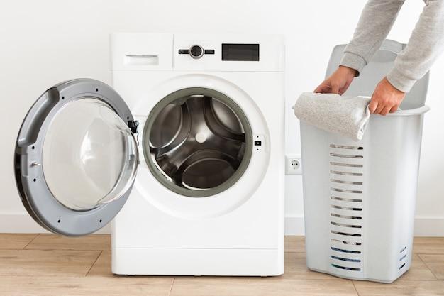 Vista laterale uomo tira fuori i vestiti dal cestino e inserendo la lavatrice nella biancheria di casa