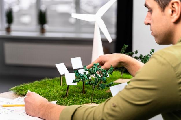 Vista laterale dell'uomo che lavora su un layout di progetto di energia eolica eco-compatibile
