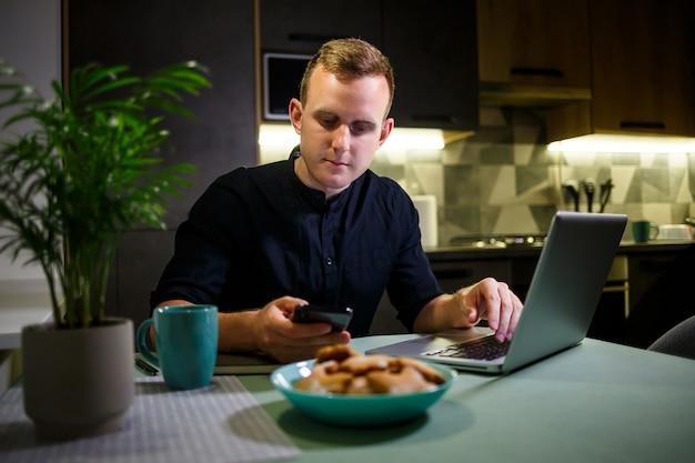 Vista laterale delle mani di un uomo che utilizza uno smartphone all'interno, un uomo impegnato con un telefono cellulare, un giovane studente seduto a un tavolo con un laptop