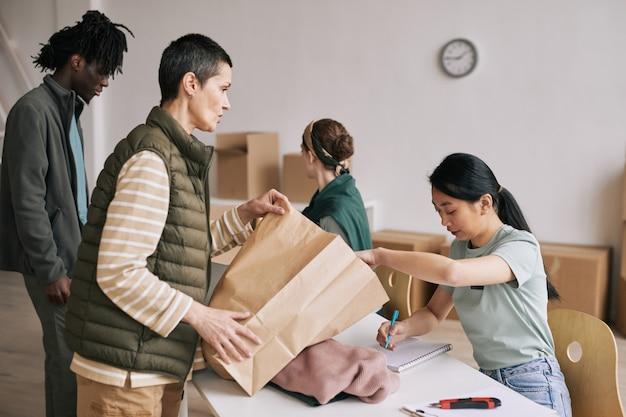 Vista laterale di una donna matura che dona cibo e vestiti all'evento di aiuto, copia spazio