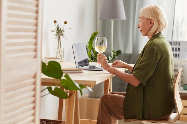Vista laterale della donna matura che si siede al tavolo con un bicchiere di vino e utilizzando il computer portatile a casa
