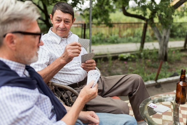 Uomini di vista laterale che giocano a carte all'aperto
