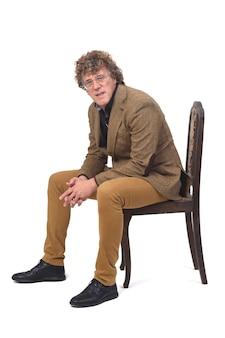 Vista laterale dell'uomo di mezza età con blazer seduto su una sedia e in posa