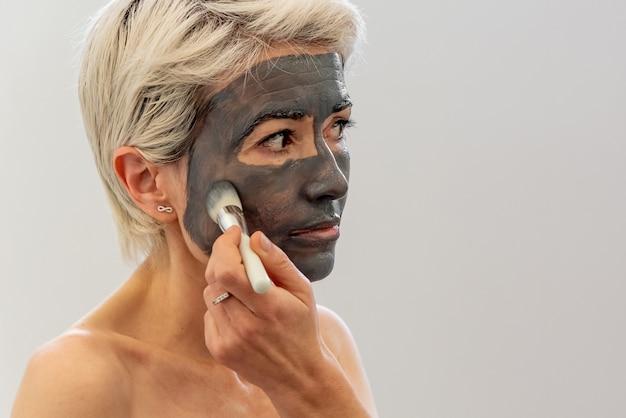 Vista laterale della donna di mezza età in asciugamano spalmando la maschera di argilla sul viso davanti allo specchio in bagno a casa