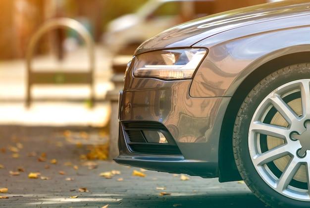 Vista laterale della moderna automobile lucida argento, parcheggiata su strada soleggiata asfaltata sotto ombroso albero verde sul fogliame sfondo bokeh di fondo.