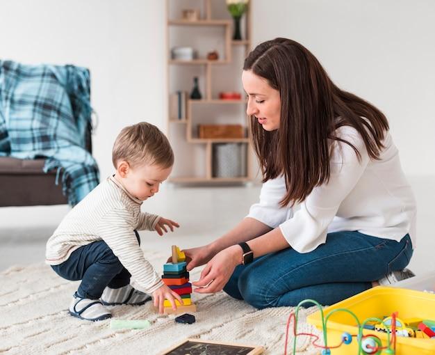 Vista laterale della mamma e del bambino che giocano con i giocattoli