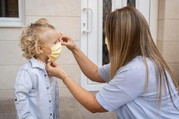 Vista laterale della mamma che mette mascherina medica sul bambino
