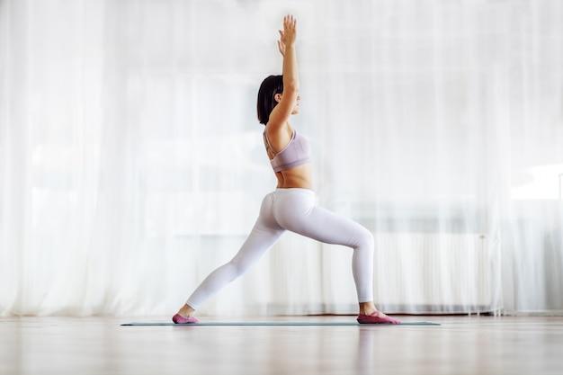 Vista laterale della bruna attraente in forma muscolare con i capelli corti in piedi nella posizione di yoga di affondo a mezzaluna. interiore dello studio di yoga.