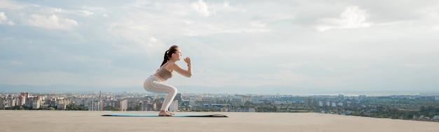 Vista laterale della giovane donna muscolare con una lunga coda di cavallo nella mattina di sole
