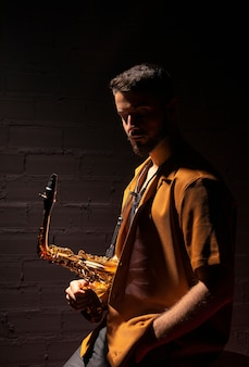 Vista laterale del musicista che tiene un sassofono