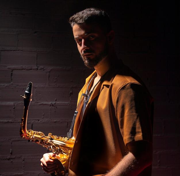 Vista laterale del musicista in posa mentre si tiene il sassofono