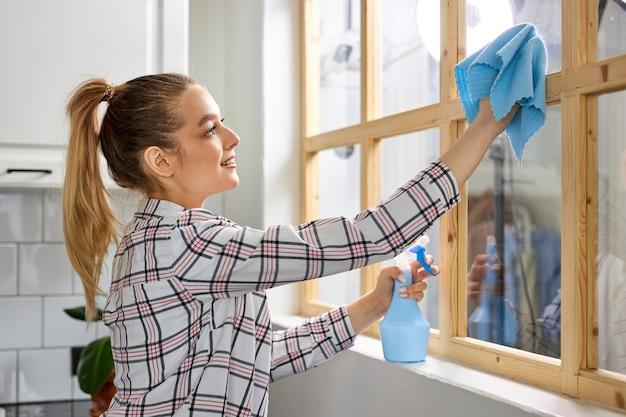 Vista laterale su nice woman pulisce il vetro, pulendo il vetro della finestra dallo sporco. strofinando con un panno e una soluzione pulita sterilizzare.