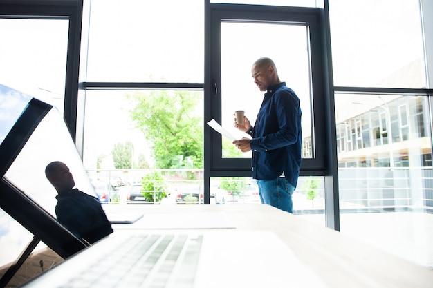 Vista laterale del posto di lavoro dell'ufficio con computer portatile e carta sul tavolo di legno.