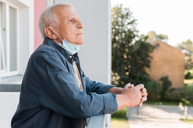 Uomo anziano di vista laterale con la maschera sul mento