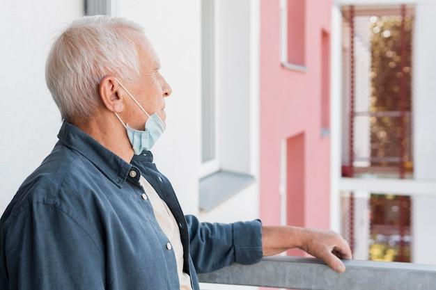 Uomo anziano di vista laterale con la maschera