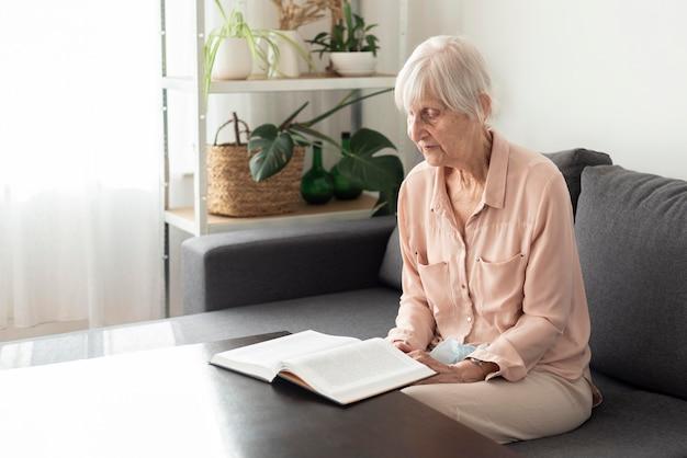 Vista laterale della donna anziana in casa di cura che legge un libro