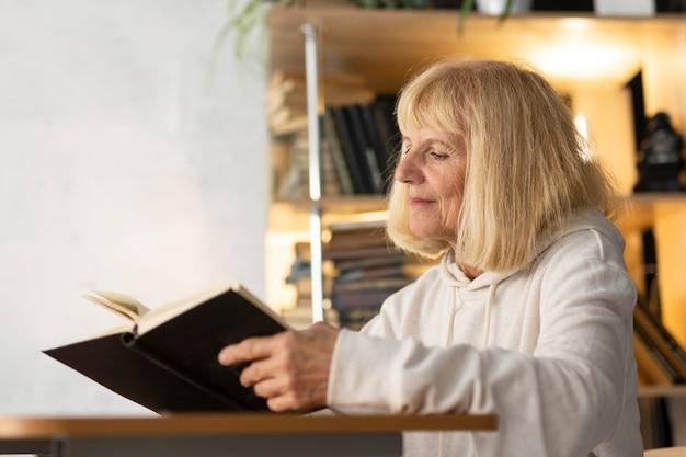 Vista laterale della donna anziana che legge un libro a casa