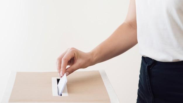 Persona di vista laterale che mette scheda elettorale nella casella elettorale