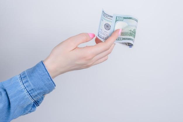 Foto di vista laterale delle mani che tengono un centinaio di dollari su sfondo grigio isolato