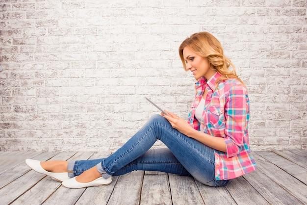 Foto di vista laterale della ragazza che si siede sul pavimento con la compressa