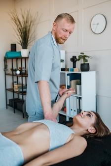 Vista laterale del fisioterapista che esegue esercizi sulla donna