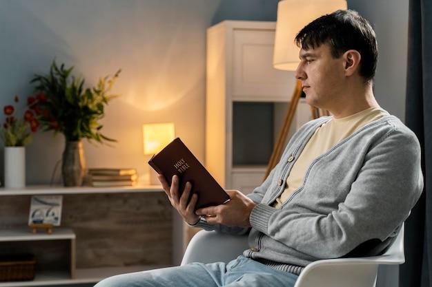 Vista laterale dell'uomo pio che legge dalla bibbia
