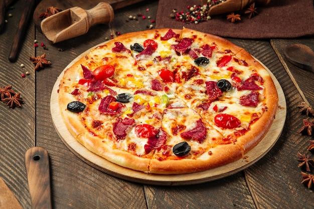 Vista laterale sulla pizza con carne affumicata e verdure sul tavolo di legno