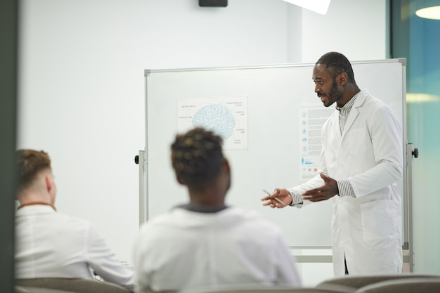 Ritratto di vista laterale di un uomo afro-americano in piedi davanti alla lavagna mentre fa una presentazione durante un seminario medico al college, copia spazio