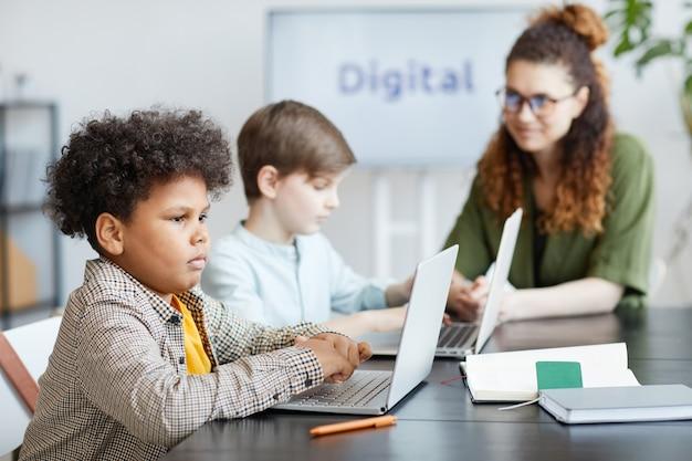 Ritratto di vista laterale di uno scolaro afroamericano che utilizza il computer in classe it, spazio di copia