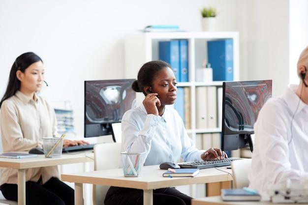 Ritratto di vista laterale della donna afro-americana che indossa l'auricolare e parla con il cliente mentre si lavora nel call center del servizio di supporto