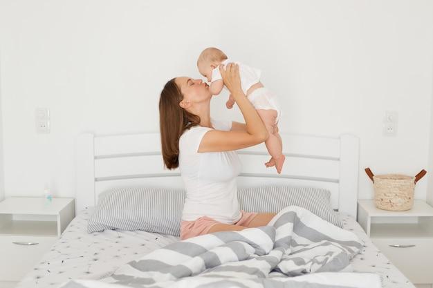 Ritratto di vista laterale di giovane madre dai capelli scura adulta attraente che tiene sua figlia infantile e che bacia il suo bambino, famiglia felice che posa nella stanza leggera sul letto.