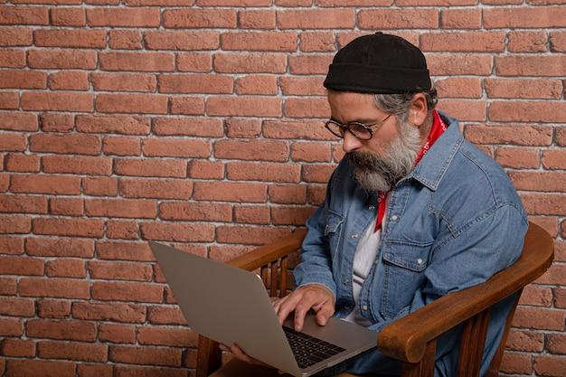 Ritratto di vista laterale dell'uomo barbuto in camicia di jeans che si siede sulla sedia di legno che lavora al computer portatile.