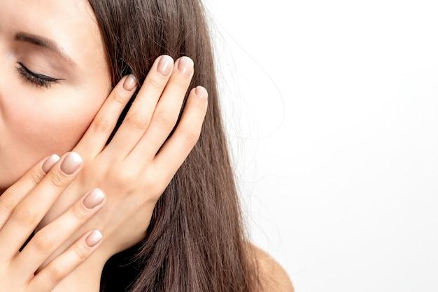 Ritratto di vista laterale di bella giovane donna caucasica del brunette con gli occhi chiusi che tocca i suoi capelli dalle dita curate sulla parete bianca
