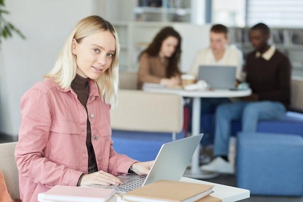 Vista laterale ritratto di giovane donna bionda mentre si utilizza il computer portatile nella biblioteca del college con persone in background,