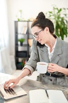 Ritratto di vista laterale della giovane donna occupata che parla dal telefono e che utilizza computer portatile mentre lavorando nell'ufficio