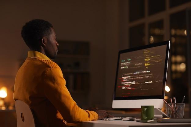 Ritratto di vista laterale dell'uomo afroamericano contemporaneo che esamina lo schermo del computer mentre lavora a tarda notte il codice di scrittura, lo spazio della copia