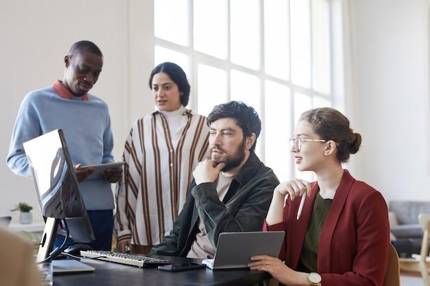 Ritratto in vista laterale di un gruppo eterogeneo di uomini d'affari che utilizzano il computer durante la pianificazione del progetto in ufficio bianco