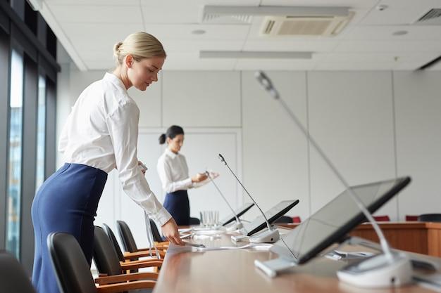 Ritratto di vista laterale della segretaria femminile elegante che mette i segnaposto sulla scrivania mentre si prepara la conferenza di lavoro in ufficio,
