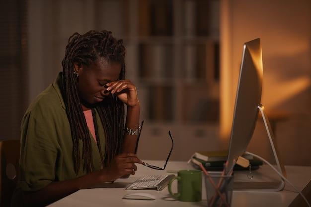 Ritratto di vista laterale della donna afro-americana esausta, strofinando gli occhi mentre si lavora a tarda notte in ufficio buio, copia dello spazio