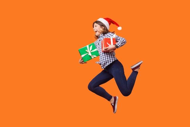 Ritratto di vista laterale di una donna bruna estremamente gioiosa con un cappello da babbo natale che salta o corre in aria con scatole regalo di natale avvolte, celebrando gli sconti. studio al coperto isolato su sfondo arancione