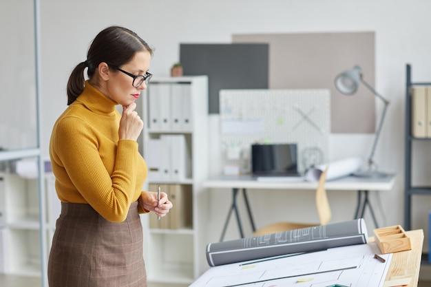 Vista laterale ritratto di donna architetto guardando le cianografie stando in piedi dal tavolo da disegno sul posto di lavoro,
