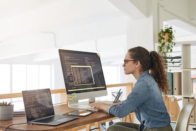 Ritratto di vista laterale di sviluppatore it femminile che digita sulla tastiera con codice di programmazione nero e arancione sullo schermo del computer e laptop nell'interiore dell'ufficio contemporaneo, spazio di copia