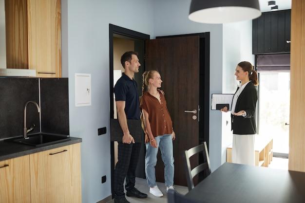 Ritratto in vista laterale di un agente immobiliare femminile che incontra una giovane coppia in piedi sulla porta mentre acquista una nuova casa, copia spazio