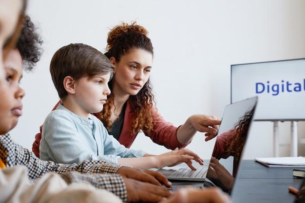Ritratto di vista laterale dell'insegnante femminile che aiuta il ragazzo a usare il laptop durante la lezione di informatica a scuola, copia spazio