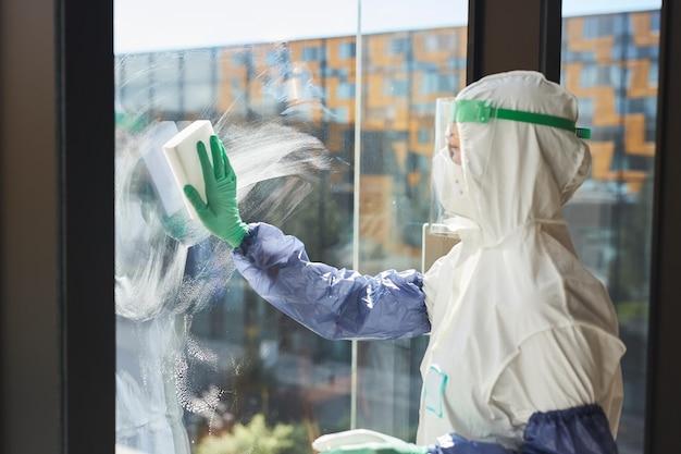 Vista laterale verticale della lavoratrice che indossa tuta ignifuga lavare i vetri e disinfettare l'ufficio in presenza di luce solare,