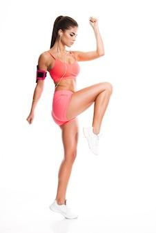 Il ritratto di vista laterale di una donna di forma fisica che fa la gamba si esercita